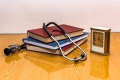 Stethoscoop en medische boeken die op een lijst liggen Stock Afbeelding