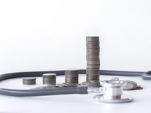 Stethoscoop en muntstukstapel op witte achtergrond geld voor gezondheidszorg, Financiële steun, concept Royalty-vrije Stock Foto's