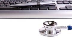 Stethoscoop en toetsenbord dat op wit wordt geïsoleerdA Royalty-vrije Stock Afbeelding