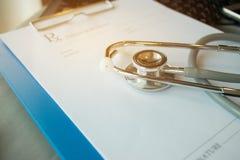 Stethoscoop en verslaginformatiedocument omslag met pen op Lapt Stock Foto