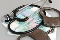 Stethoscoop, handcuffs en geld op grijs Stock Foto's