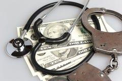 Stethoscoop, handcuffs en geld op grijs Stock Afbeeldingen