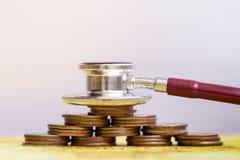 Stethoscoop met muntstukkenstapel op witte achtergrond het medische kosten toenemen royalty-vrije stock afbeelding