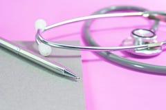 Stethoscoop met pen op leeg notitieboekje op roze achtergrond royalty-vrije stock afbeeldingen