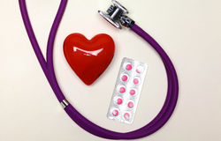 Stethoscoop met pillen en rood die hart op witte achtergrond worden geïsoleerd Royalty-vrije Stock Afbeeldingen