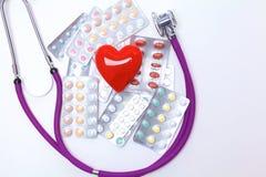 Stethoscoop met pillen en rood die hart op witte achtergrond worden geïsoleerd Royalty-vrije Stock Afbeelding