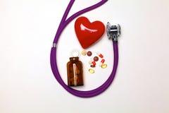 Stethoscoop met pillen en rood die hart op witte achtergrond worden geïsoleerd Stock Foto's