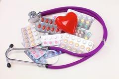 Stethoscoop met pillen en rood die hart op witte achtergrond worden geïsoleerd Stock Fotografie