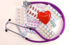 Stethoscoop met pillen en rood die hart op witte achtergrond worden geïsoleerd Stock Foto