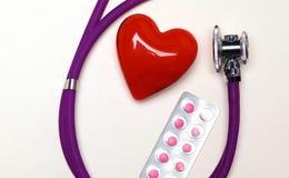 Stethoscoop met pillen en rood die hart op witte achtergrond worden geïsoleerd Stock Afbeelding