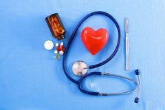 Stethoscoop met pillen en rood hart op lijstachtergrond Stock Fotografie