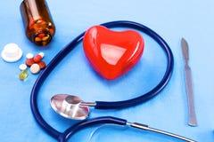 Stethoscoop met pillen en rood hart op lijstachtergrond Stock Afbeeldingen