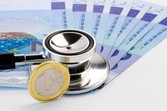 Stethoscoop op bankbiljet dichtbij euro muntstuk Royalty-vrije Stock Foto's