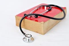 Stethoscoop op rood oud boek Stock Afbeeldingen