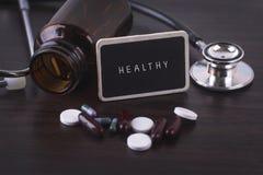Stethoscoop, pillenfles, Diverse pillen, capsules en GEZOND op houten achtergrond met copyspacegebied Stock Foto's