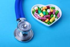 Stethoscoop, RX-voorschrift en kleurrijke assortimentspillen en capsules op plaat royalty-vrije stock foto