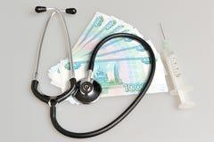 Stethoscoop, spuit en geld op grijs Royalty-vrije Stock Afbeelding