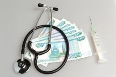 Stethoscoop, spuit en geld op grijs Royalty-vrije Stock Foto's
