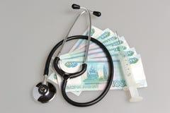 Stethoscoop, spuit en geld op grijs Stock Foto