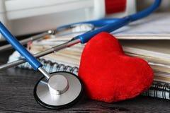 Stethoscoop voor arts en medische pleegmensen in het ziekenhuis, het helen van patiënten Houten achtergrond en rood hart Royalty-vrije Stock Afbeelding