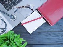 Stethoscooplaptop van de het notitieboekjemening van de bladdesktop hoogste van het de werkplaatsblad zwarte houten Stock Afbeeldingen