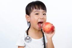 亚裔矮小的中国女孩装饰了作为有Stethoscop的医生 免版税图库摄影