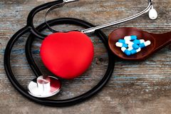 Stethoscop, red heart and medicine pills, capsules on wooden spoon closeup. Concept treatment of heart disease pills.  stock image