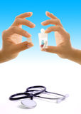 Stethoscope. A stethoscope and two hands holding medications Royalty Free Stock Photos