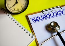 NEUROLOGY on top of yellow background. A stethoscope, alarm clock and notebook with word NEUROLOGY on top of yellow background. Medical, health and education stock image