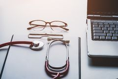 Free Stethoscope And Glasses On Laptop With Clipboard Blank Paper Stock Photo - 119025310