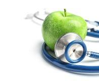 Stethoscope and apple on light background. Medical equipment Stock Image