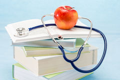 Stethoscope and apple medical healthcare. Healthy lifestyle doctor book Stock Photography