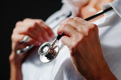 Stethoscope Around Neck. Close up of stethoscope being held by older womans hands stock photography