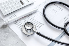 Stethoscope, billing statement for doctor`s work in medical center stone background. Stethoscope, billing statement for doctor`s work in medical center on stone Royalty Free Stock Image