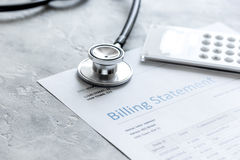 Stethoscope, billing statement for doctor`s work in medical center stone background. Stethoscope, billing statement for doctor`s work in medical center on stone Royalty Free Stock Photos