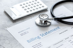 Stethoscope, billing statement for doctor`s work in medical center stone background. Stethoscope, billing statement for doctor`s work in medical center on stone Royalty Free Stock Photography