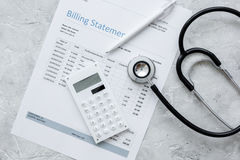 Stethoscope, billing statement for doctor's work in medical center stone background top view. Stethoscope, billing statement for doctor's work in medical center Stock Photo