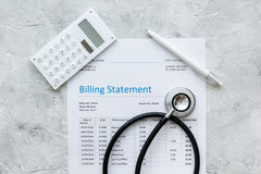 Stethoscope, billing statement for doctor's work in medical center stone background top view. Stethoscope, billing statement for doctor's work in medical center Stock Image