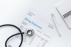 Stethoscope, billing statement for doctor's work white background top view. Stethoscope, billing statement for doctor's work in medical center on white Stock Photo