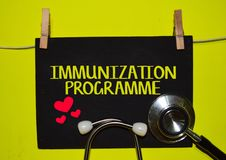 IMMUNIZATION PROGRAMME on top of yellow background. A stethoscope and blackboard with word IMMUNIZATION PROGRAMME on top of yellow background. Medical, health stock photo