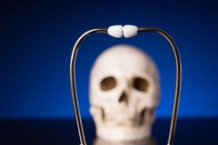 Stethoscope and blurry skull. Stethoscope i focus and blurry skull isolated on black blue background stock image