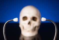 Stethoscope and blurry skull. Stethoscope i focus and blurry skull isolated on black blue background stock photo