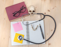 Stethoscope , book note and skull Stock Photo