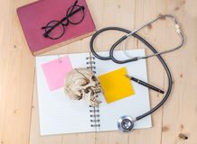 Stethoscope , book note and skull Stock Photography