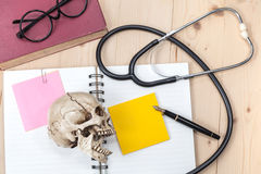 Stethoscope , book note and skull Stock Image