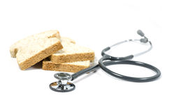 Stethoscope and bread  on white Royalty Free Stock Image