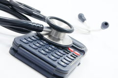 Stethoscope with calculator. Stethoscope with black calculator on white background Stock Images