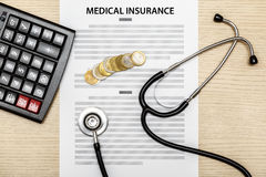 Stethoscope and calculator and coins laying on the blank of medi Stock Images