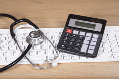 Stethoscope and calculator on a computer keyboard. In a concept of the cost of online medicine of of troubleshooting and repair to the hardware Royalty Free Stock Photos