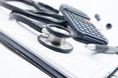 Stethoscope with calculator, pen and book Stock Photos